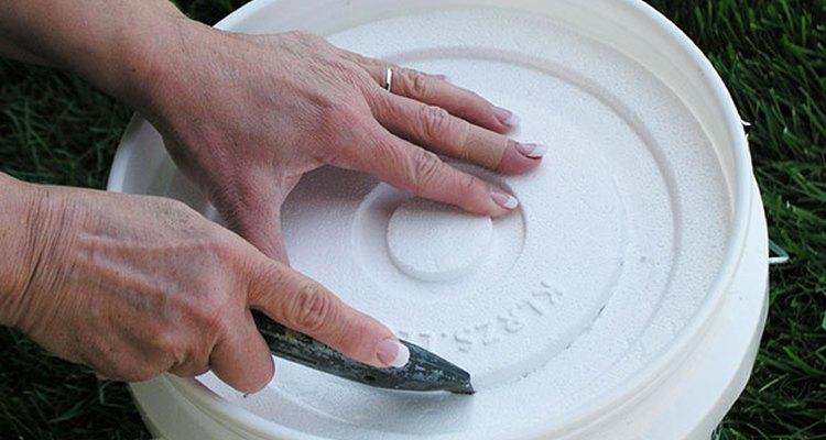 Recorta un agujero en la tapa de la cubeta de espuma de poliestireno.