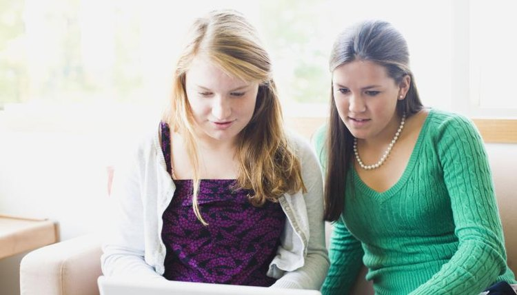 Two girls working on a laptop at home.