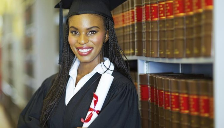 Graduating African-American in library with degree in hand