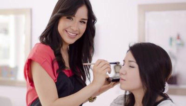 Makeup artist working on client.