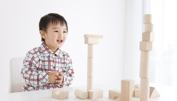 Smiling young preschool boy with building blocks.