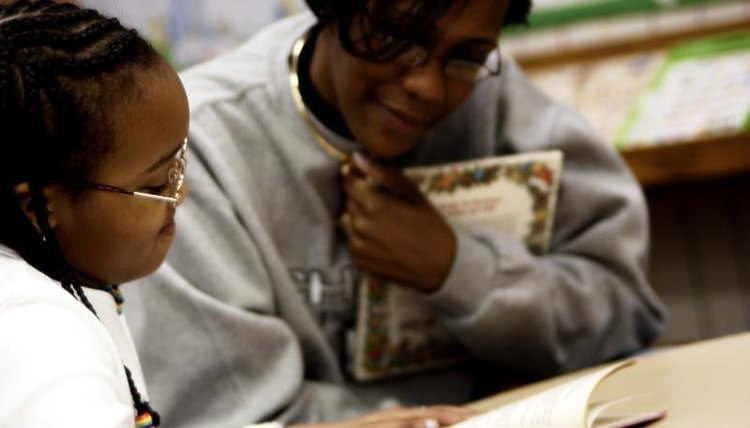 Teacher reading book with young student in classroom.