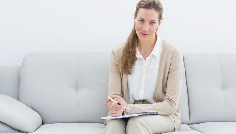 An Adlerian therapist sitting on couch with clipboard in hand.