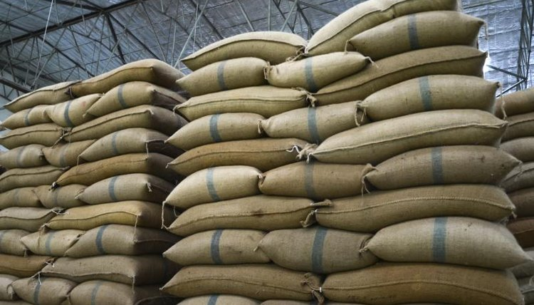 A tall stack of bags of rice in a warehouse
