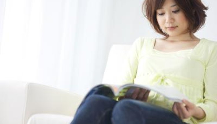 Young woman reading journal on couch.