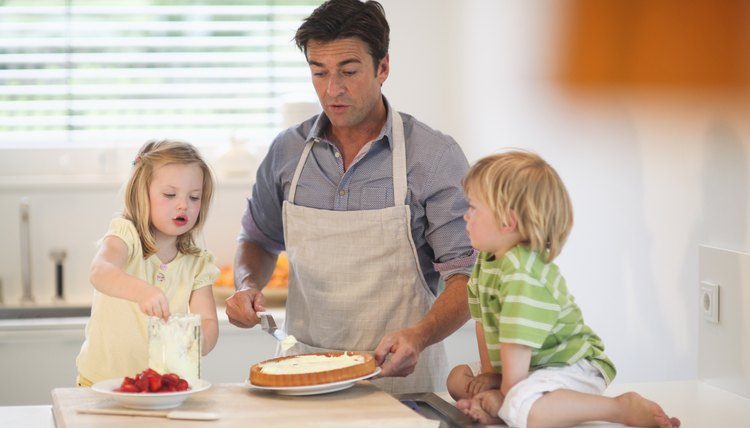 Mature man and son and daughter making cake in kitchen