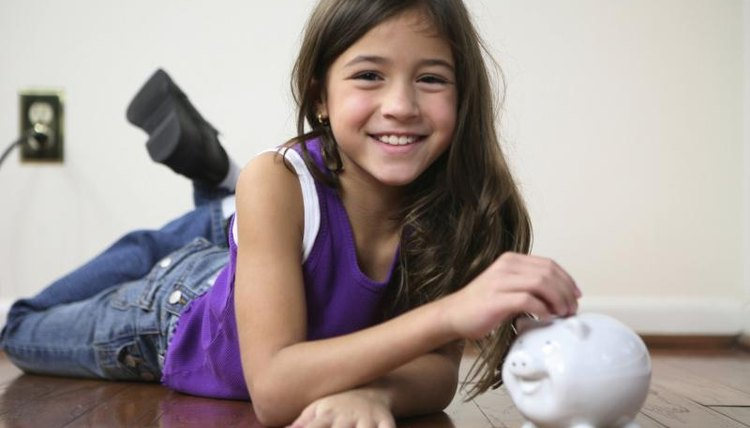 A young girl, coins, a piggy bank