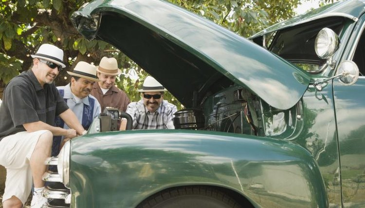 Group of men looking at engine of restored classic vehicle