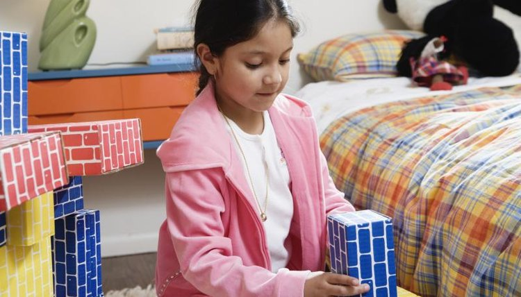 Child playing with blocks in bedroom.