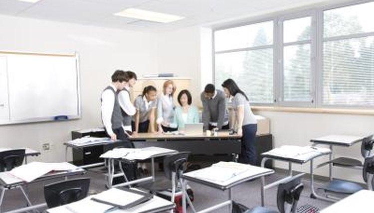 High School students are standing around their teachers desk.