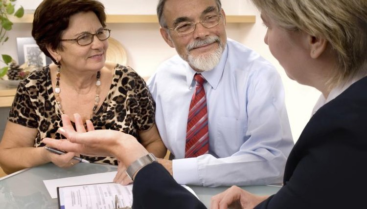A senior couple discusses documents with an attorney.