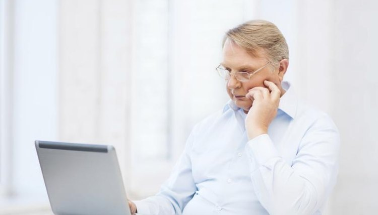 Older teaching typing at laptop