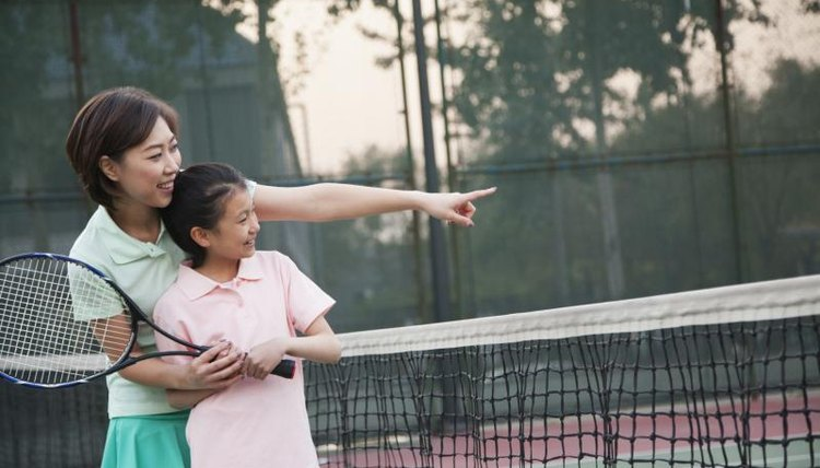 A young girl is learning how to play tennis.