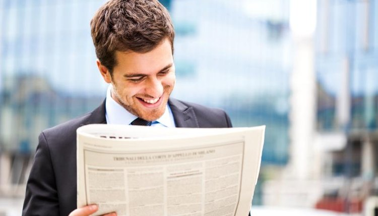 Man reading newspaper article.