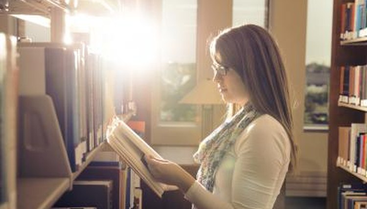 A young woman is in the library studying.