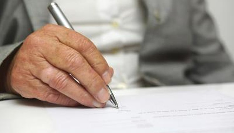 Image of an older person signing a document.