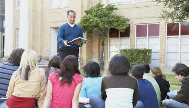 Teacher speaking to students outside on lawn