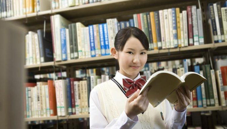 High school student holding book open in library.