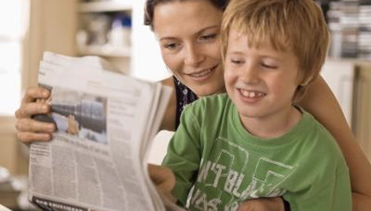 Mother and son looking at newspaper