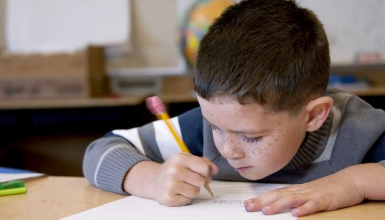 how to teach kids to write introductions conclusions for an  an elementary student writing at a classroom table