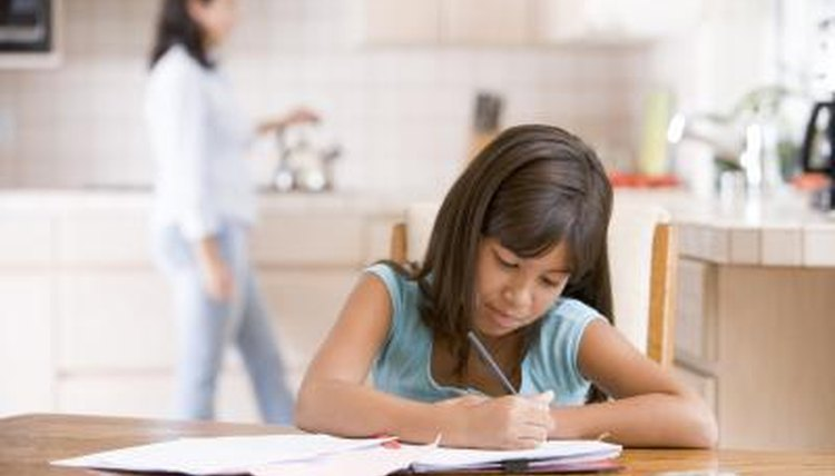 Young girl doing an assignment with mother in background.