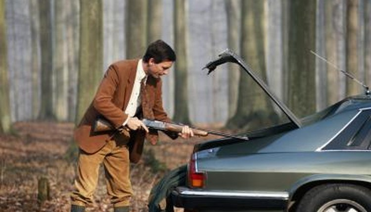 Man taking rifle from trunk of automobile