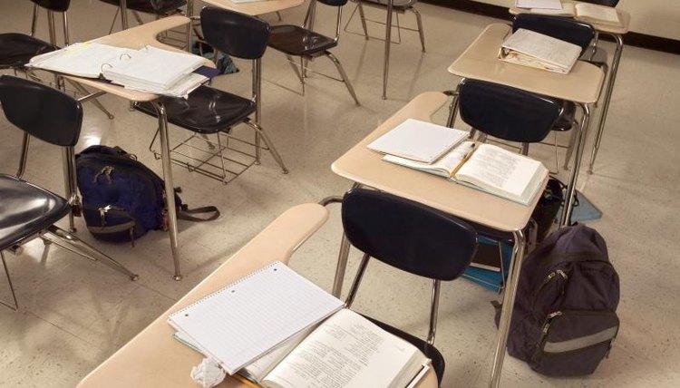 Empty classroom with desks and workbooks.