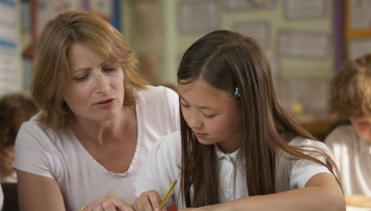 Teacher helping young student sound out a word at her desk