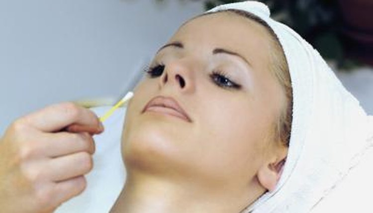 An adult woman is receiving a beauty treatment from a cosmetologist.