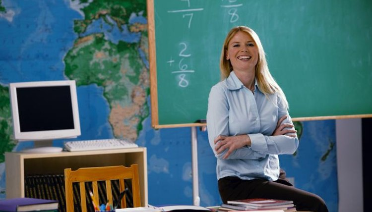 Smiling young teacher standing in front of chalk board with basic math problems written on it