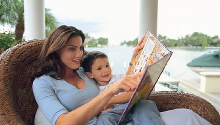 Young child reading picture book with mother