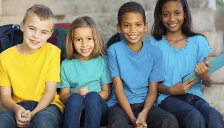 Group of diverse children from different backgrounds sitting together on cement steps