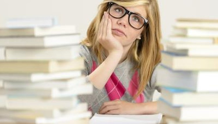 Student studying for exam with piles of books.