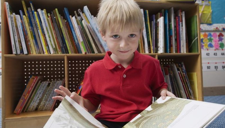 Young boy holding open book in classroom.