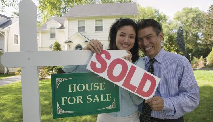 "Happy couple standing in front of a house with a ""sold"" sign."