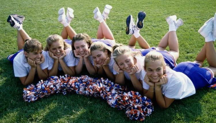 Smiling young cheerleaders on grass.