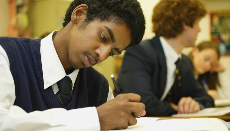 Student in school uniform working at desk.