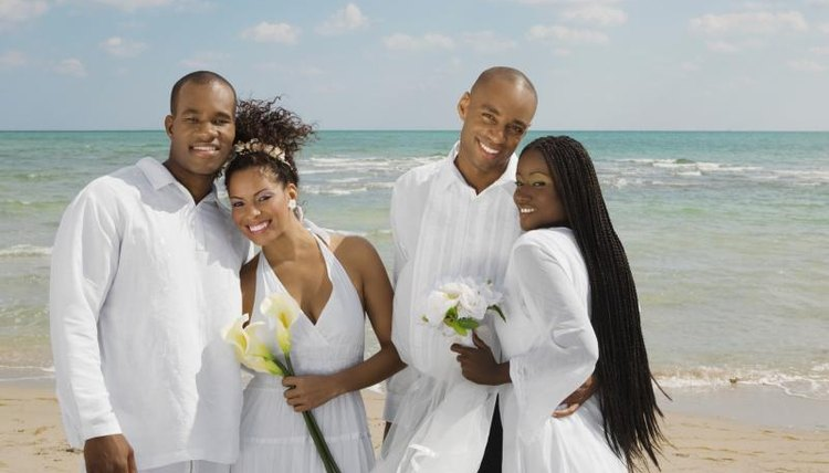 Smiling brides on beach with newlywed husbands.