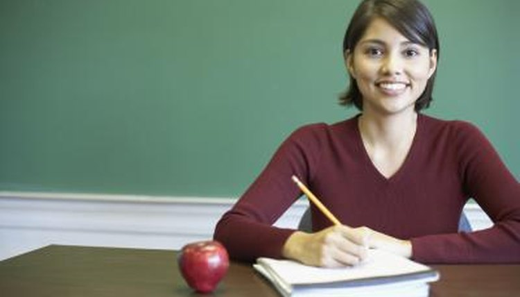 A smiling teacher is at her desk.