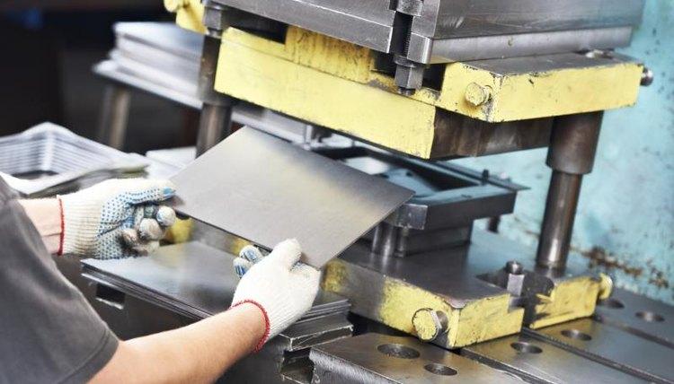 Close-up of man using sheet metal press