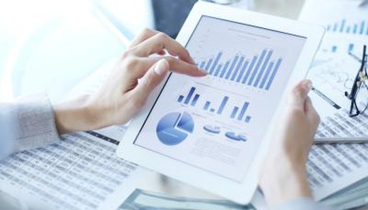 Close-up of woman holding iPad with different graphs on screen