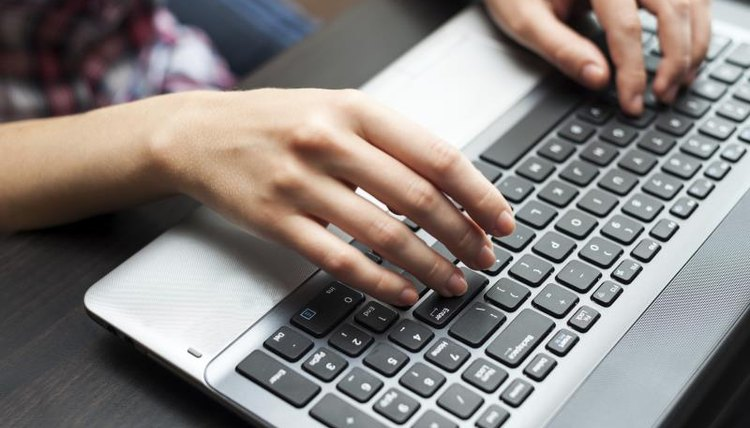 Student typing on a laptop