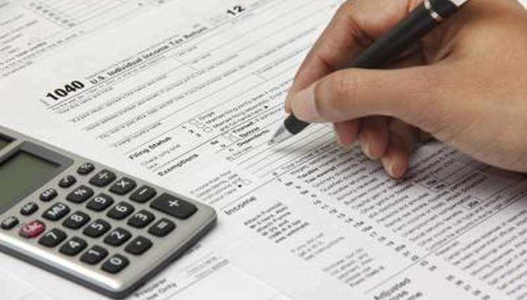 Close-up of a man filling out tax forms with a pen.