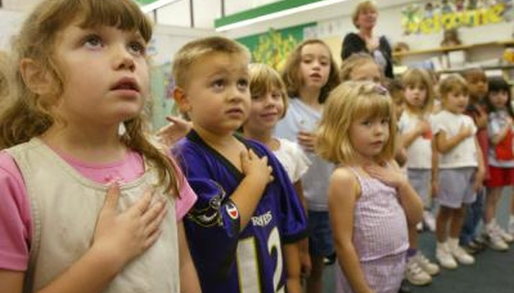 A kindergarten class reciting the Pledge of Allegiance with their hands on their hearts.