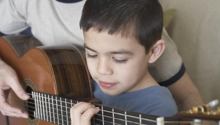 Young boy learning to play the guitar.