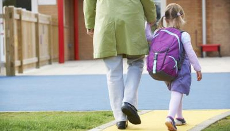 A young girl walks with her parent to school.