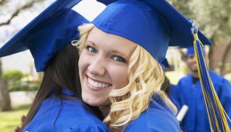 Close-up of smiling graduate hugging her classmate.