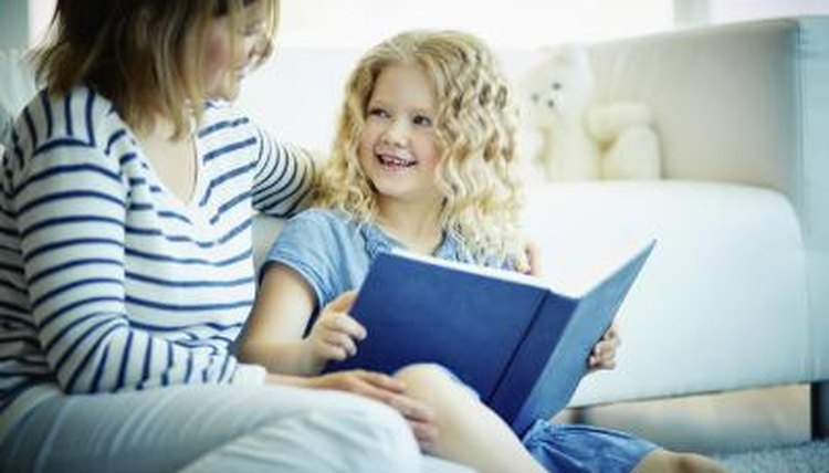 Parent sitting child on couch with book in hand