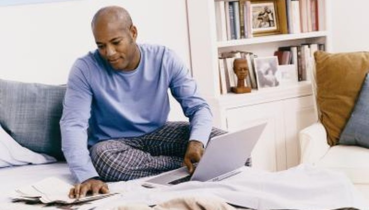 Man studying at home on laptop.