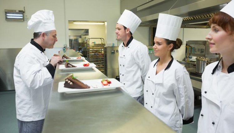 Chef examining culinary students' food.